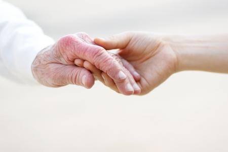 Senior dame en jonge vrouwen hand in hand Stockfoto