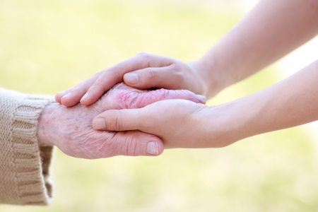 helping people: Senior lady and young women holding hands