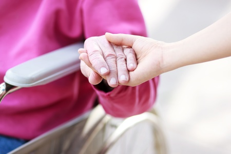 Senior Lady in Wheelchair Holding Hands with Caretaker photo