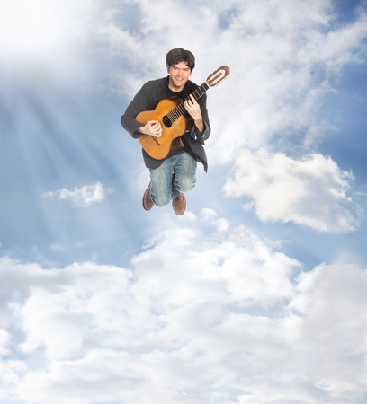 Acoustic Guitar Player Jumping in the Clouds photo