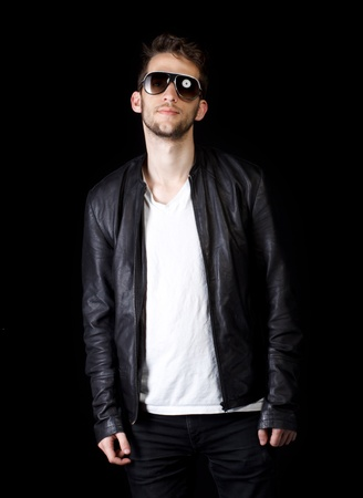 Portrait of young handsome man wearing sunglasses on black background photo