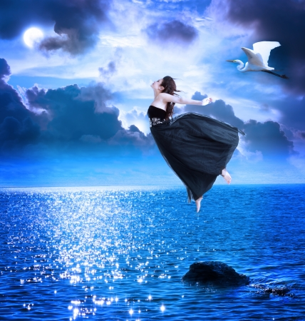 woman flying: Beautiful girl jumping into the blue night sky with white egret
