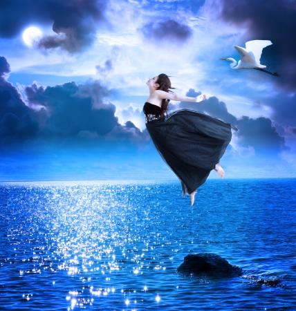 donna volante: Bella ragazza che salta nel cielo blu notte con bianco egret