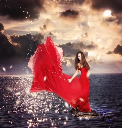 Beautiful Girl in Red Dress Standing on Ocean Rocks