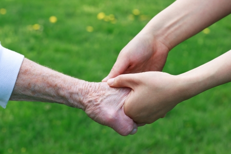 help: Senior and Young Women Holding Hands Outside