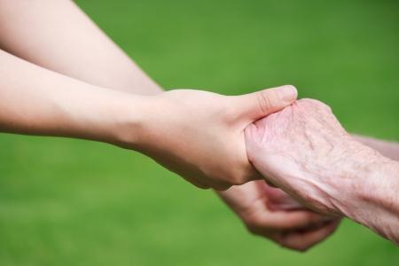 segítség: Senior és fiatal nők Holding Hands Outside