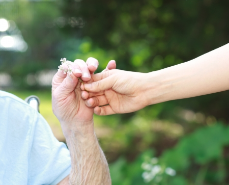 Giving a white flower to senior lady outside photo