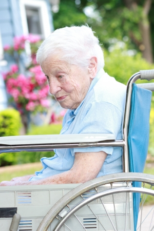 Senior lady in wheel chair in front of house with pink flowers photo