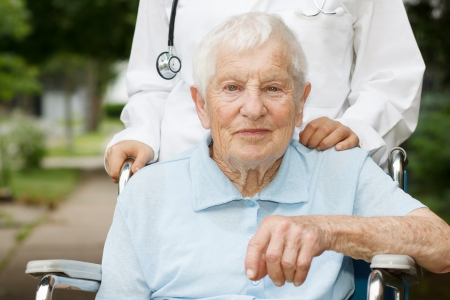Happy senior lady in wheelchair with her caregiver photo