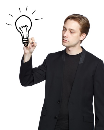 Man drawing a light bulb with black marker photo
