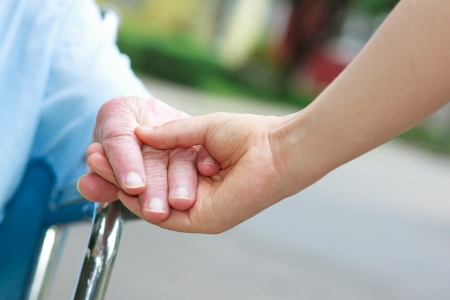Senior women in wheelchair holding hands with caretaker photo