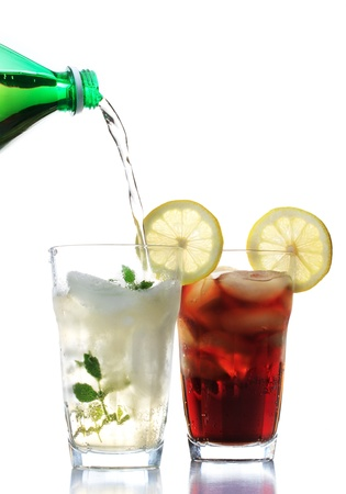 Ginger ale and cola in the glasses with lemon garnish photo