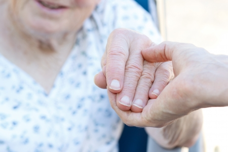 happy old age: Senior woman in wheelchair holding hands with caretaker Stock Photo