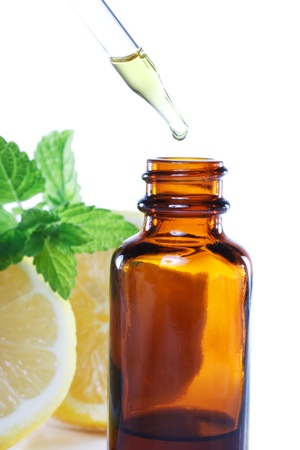 Herbal medicine dropper bottle with mint leaves and lemon
