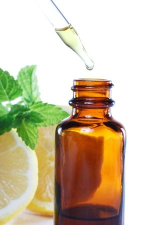 elixir: La medicina herbaria frasco gotero con hojas de menta y limón Foto de archivo