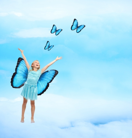 releasing: Happy Young Girl in Blue Dress with Arms in the Air Releasing Butterflies  Stock Photo