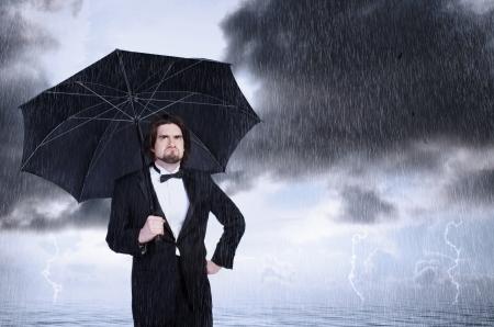 uomo sotto la pioggia: Infelice Tenendo Umbrella in una tempesta di pioggia e accigliato