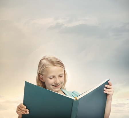 Little Blonde Girl Reading a Big Blue Book photo