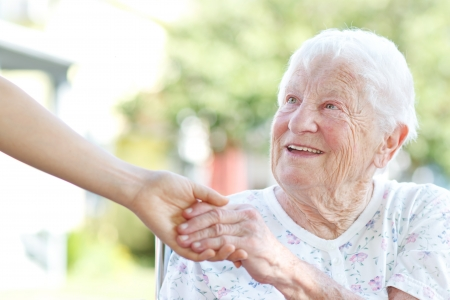 Happy senior woman holding hands with caretaker photo