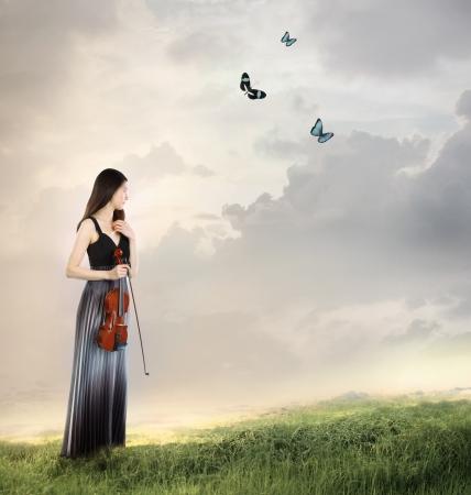 violinista: Jugador del viol�n en la cima de una monta�a con las mariposas Foto de archivo
