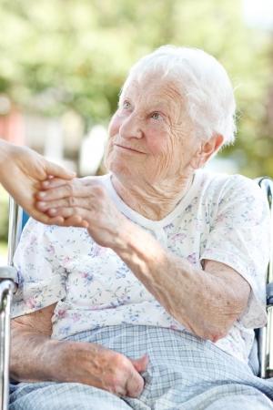 caretaker: Happy senior woman holding hands with her caretaker Stock Photo