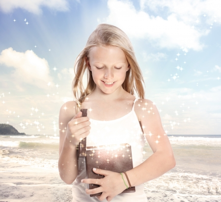 Happy Young Blonde Girl Opening a Gift Box on the Beach photo