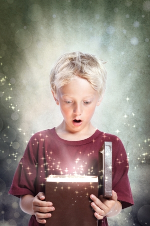 Happy Young Blonde Boy Opening a Gift Box Stock Photo - 14532686