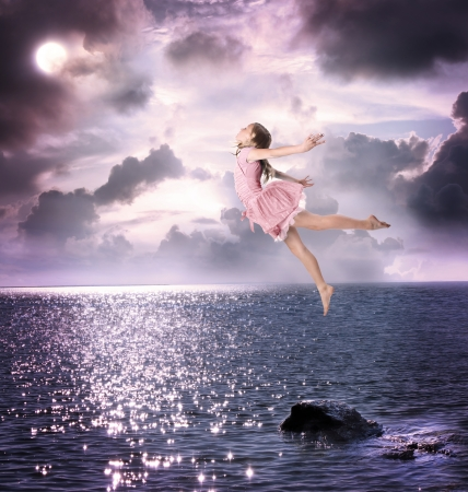 woman flying: Little Blonde Girl Flying Into the Night Sky Stock Photo