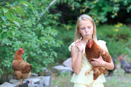 Young Blonde Girl in the Garden with Chickens in a Yellow Dress