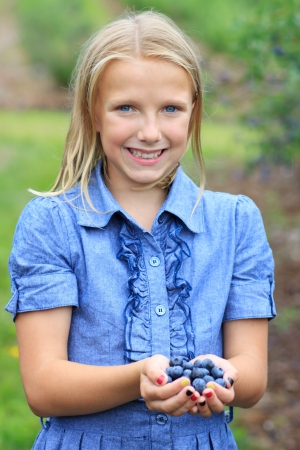 Young Blonde Girl Holding Fresh Picked Blueberries in a Blue Dress Smiling