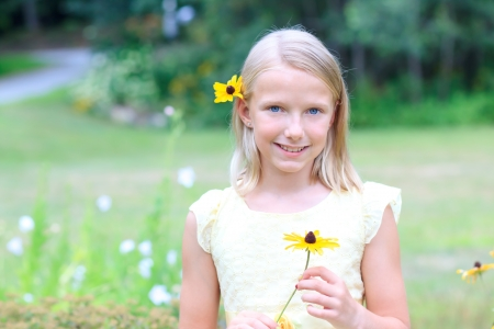 cute young farm girl: Young Blond Girl Holding a Flower in her Hands