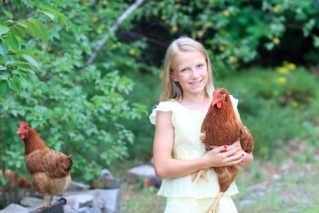 Young Blonde Girl in the Garden caring for Her Chickens in a Yellow Dress Stock Photo