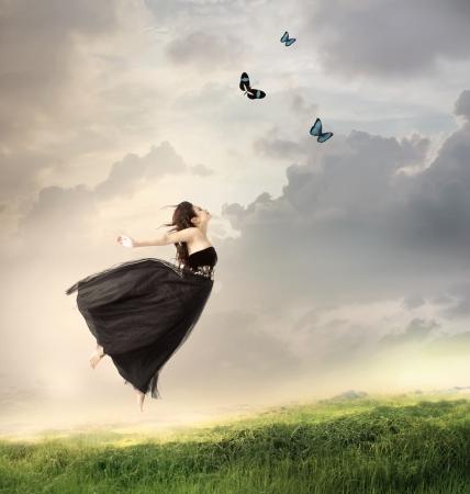 donna volante: Bella ragazza saltare in aria su una montagna