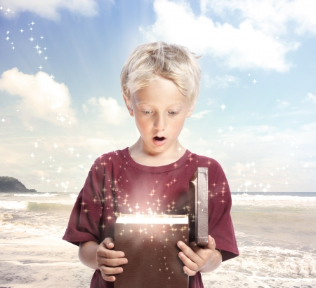 surprised child: Happy Young Blonde Boy Opening a Gift Box on the Beach