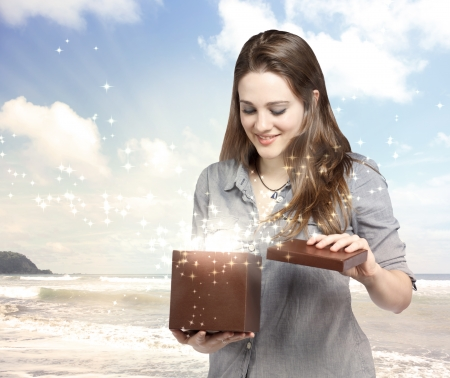 christmas magic: Happy Young Woman Opening a Gift Box