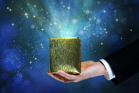 Business man holding a magic box on shiny blue background photo