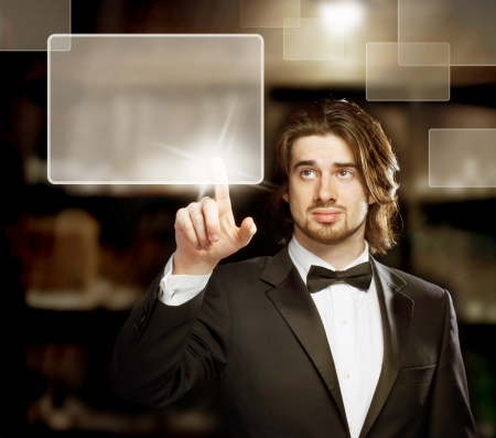 Man with Bow Tie  Looking and Pointing a Touch Screen photo