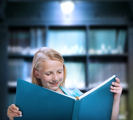 Little Girl Reading a Big Book in a Library photo