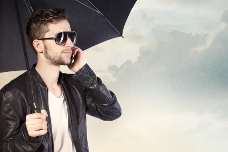 Stylish Man Holding an Umbrella and Talking on His Phone photo