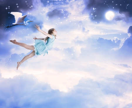 Little girl flying into the blue night sky with white egret photo