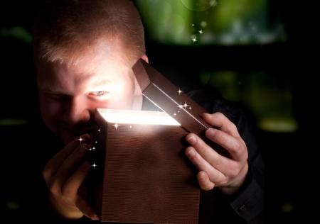 Hombre Abrir una caja de regalo Shinning Foto de archivo