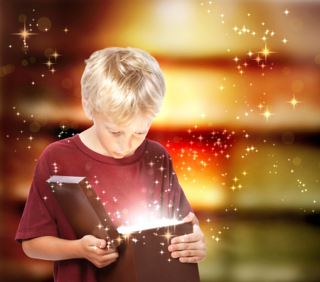 ギフト用の箱を開いて幸せな若い金髪の少年 写真素材