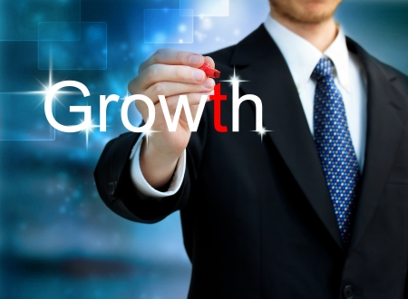 Young business man writing the word Growth with red pen photo