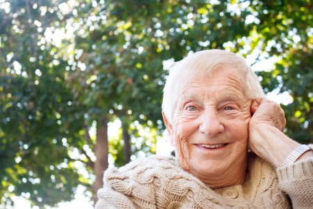 80 plus adult: Happy senior lady smiling outside
