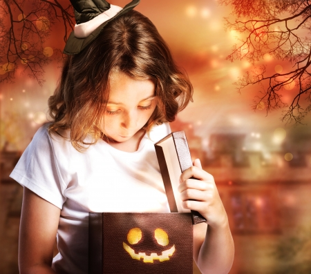 cute little girl smiling: Halloween Cute Little Witch Opening a Box