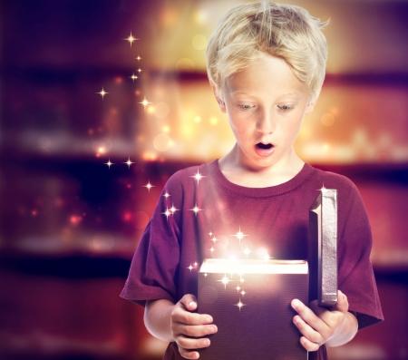 cara sorprendida: Feliz muchacho joven rubio Abrir una caja de regalo Foto de archivo