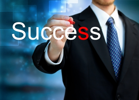 Young business man writing the word Success with red pen photo