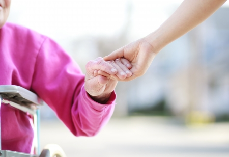 高齢女性の世話人と手を繋いでいる車椅子
