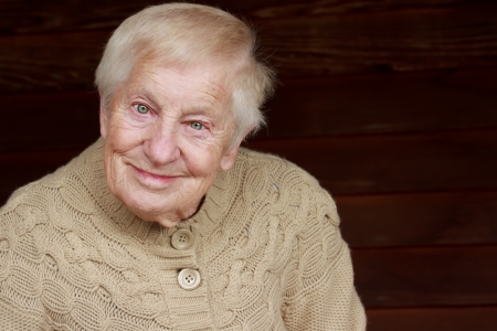80 plus years: Happy senior lady in beige sweater smiling