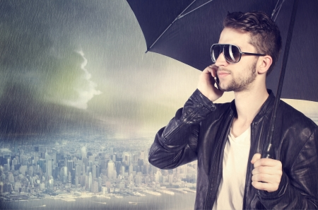 Stylish man talking on his cellphone in the rain photo